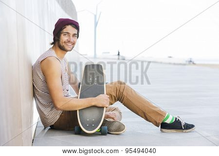 Side view portrait of happy man sitting with skateboard on footpath