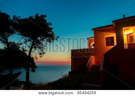 Sunset view to sea from Greek house patio with pine trees