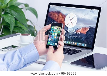 Apple Iphone With Ios 9 In Male Hands And Macbook Pro Retina With Os X El Capitan On The Office Desk