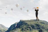 image of spyglass  - Young woman engineer on rock top looking in spyglass - JPG