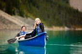 stock photo of canoe boat man  - A portrait of a happy woman on a canoeing trip with a man - JPG