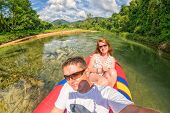 picture of rainforest  - Young couple making a selfie shot while canoeing in Kao Sok rainforest river - JPG