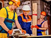 pic of millwright  - Happy group people  of three people builder with circular saw - JPG