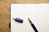 picture of memento  - Opened notebook with a blank sheet and pen on the old tissue - JPG