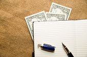 picture of memento  - Opened notebook with a blank sheet pen and money on the old tissue - JPG