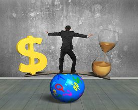 image of seesaw  - Man standing between hourglass and golden dollar sign balancing on seesaw of wood board and colorful ball with concrete wall and wooden floor indoors background - JPG