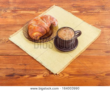 Freshly brewed coffee latte in a black ceramic cup and croissant on a glass saucer on a placemat on an old wooden surface