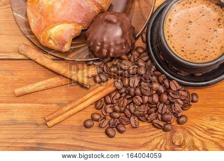 Fragment of black ceramic cup with freshly brewed coffee closeup on the background of roasted coffee beans cinnamon sticks chocolate truffle and croissant on a wooden surface