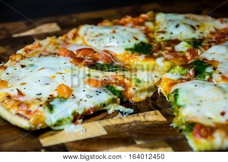 Pesto Mozzarella Herbs and Tomato Pizza Pie close up  on an acacia wood cutting board melted cheese with slice missing