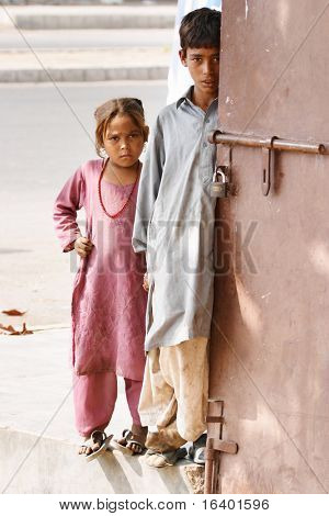 PAKISTAN, KARACHI - NOVEMBER 14: Children from poor neighborhoods, November 14, 2006 in Karachi, Pakistan. Two needy pakistani children standing at the door of the shop and waiting for charity on November 14, 2006 in Pakistan, Karachi