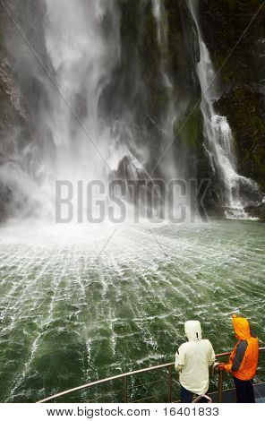 People on the boat near spectacular waterfall, Milford Sound fiord, New Zealand