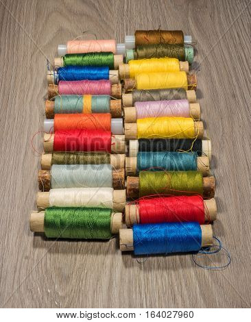 Sewing thread reels on a wood textured background. Bobbins of thread lined up in a row.