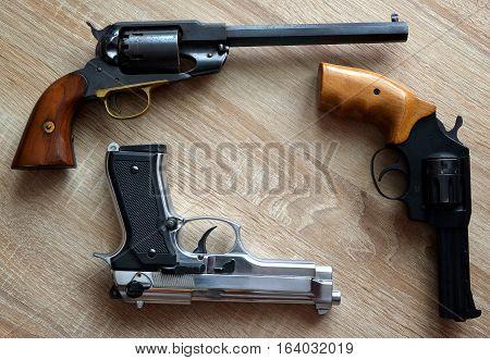 Three metallic  pistols on a wooden board.