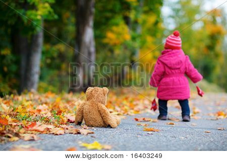 Cute 1 year old girl walking outdoors at autumn day. Focus on teddy bear