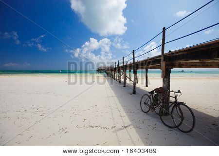 Wooden jetty on white sand tropical beach on Zanzibar island