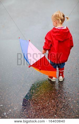 Vista de criança menina de volta ao ar livre em dia chuvoso