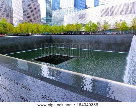 New York CITY, United States of America - May 01, 2016: New York City, Memorial at Ground Zero, Manhattan, commemorating the terrorist attack of September 11, 2001. Flowers near the names of victims engraved in the bronze parapet.