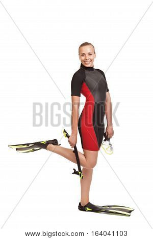 Young smiling blond woman in a wet suit for swimming is in the full-length standing on one leg holding flippers and snorkel.Studio short. Isolated on white background.