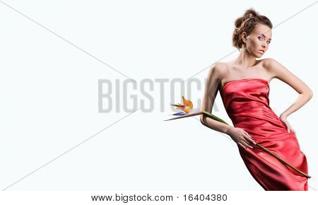 beautiful girl in a long red dress holds an exotic flower in a hand