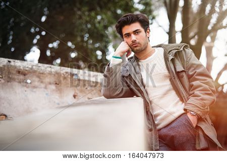 Handsome young bored man leaning on a wall. Outdoor. A handsome young man is leaning on a wall. Arm rests his hand on his cheek. The other hand in his pocket. Outdoors in a park.
