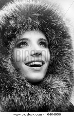 Portrait of the beautiful, smiling young woman with a fur hood.