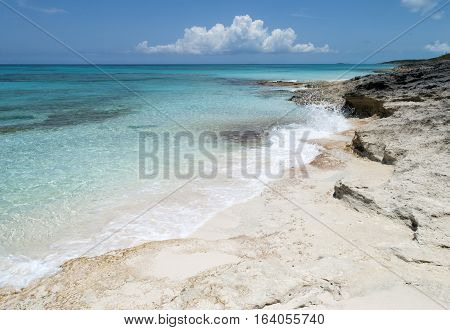 Small waves hitting rocky beach on uninhabited island Half Moon Cay (The Bahamas).