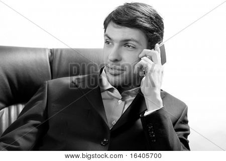 Close-up portrait of a successful handsome business man talking on cell phone. Over white background.