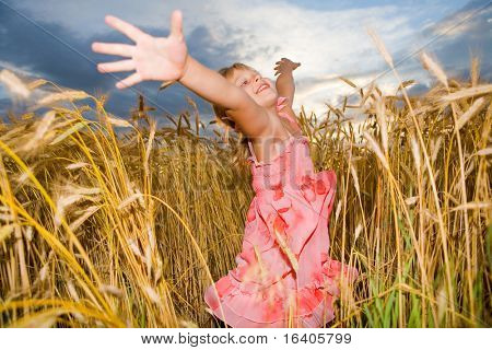 Little girl jumps in a wheat field. Against backdrop of cloudy skies