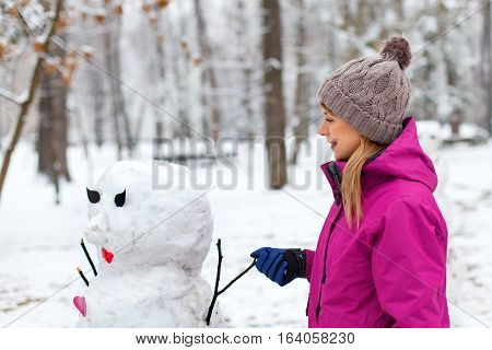 Picture of a cute girl posing next to a snowman