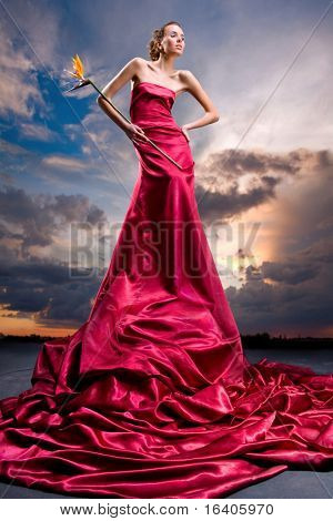 Beautiful girl in a long red dress holds an exotic flower in a hand. Against backdrop of cloudy skies