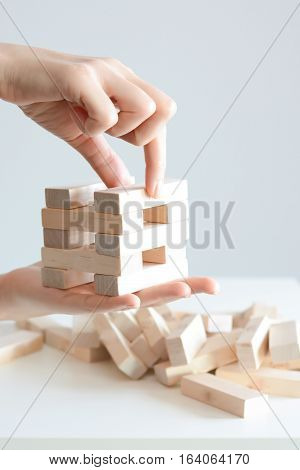 Woman hand constructing a tower of wooden blocks on a white background