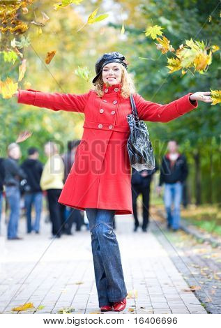 happy woman in red coat throwing leaves in the air