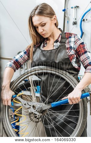 Concentrated on the result. Muscular strong charming craftswoman standing in the workshop and working while fixing the wheel and holding instruments