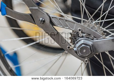 Fixing of the bicycle chain. Strong athletic young master standing in the garage and working while fixing the chain of the bicycle and holding different tools