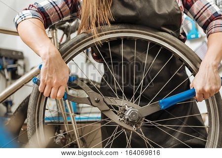 Talented craftswoman working. Muscular athletic young craftswoman standing in the repair shop and working while fixing the chain of the bicycle and holding different tools