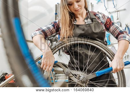 Strong athletic young worker standing in the garage and working while fixing the chain of the bicycle and holding different tools