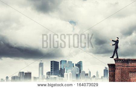 Businessman with blindfolder on eyes walking on building top