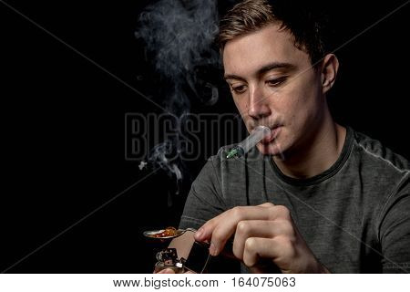 Caucasian teen boy melting illegal drugs ready for use
