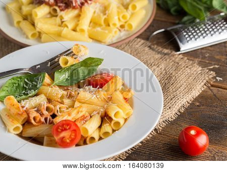 Serving pasta with tomato sauce and parmigiano on wooden table.