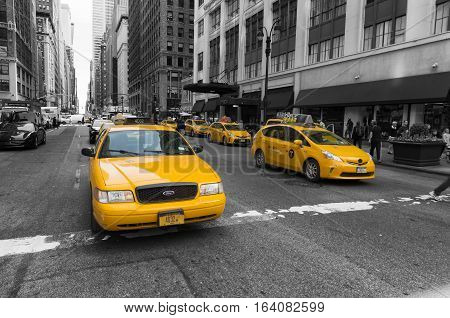 NEW YORK - APRIL 28 2016: Typically yellow medallion taxicabs in front of Macy's department store. They are widely recognized icons of the city and come in two varieties: yellow and green.
