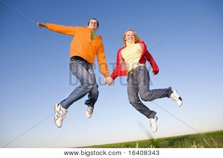 Happy young couple  jumping in sky