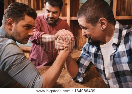 Fixed gaze. Handsome serious concentrated men looking at each other and gathering their strength while preparing to start an armwrestling match