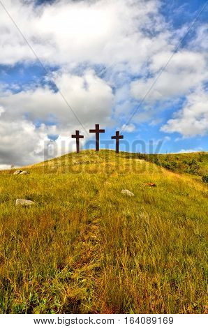 Three crosses on a grassy hill with a bright cloudy blue sky, to represent the crucifixion of Jesus.