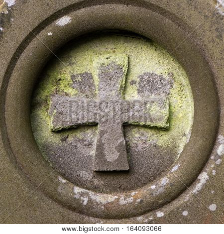 St. John's cross carved on gravestone. Christian symbol also known as the Maltese Cross Pattée Cross adorning headstone in English churchyard