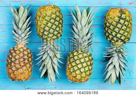 Four pineapple fruits arranged alternating next to each other on old blue crackled wooden market table