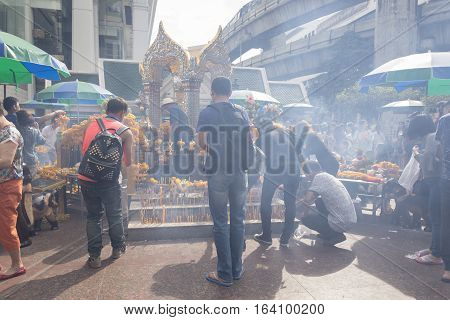 BANGKOKTHAILAND - DEC 31 : incense smoke scene from tourist worship in Erawan shrine while new year festival on december 31 2016 Thailand. Erawan shrine is famously place in ratchaprasong area
