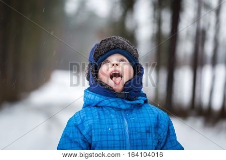 Happy Little Boy Playing Outdoor In Winter Snow. Boy Catching Snow With His Tongue