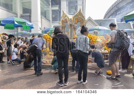BANGKOKTHAILAND - DEC 31 : snapshot of tourist pray at Erawan shrine in ratchaprasong area on december 31 2016 Thailand. there are many tourist worship at Erawan shrine in new year festival