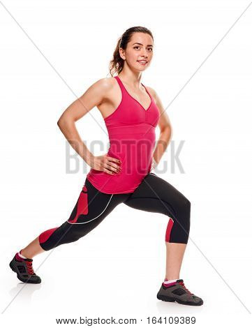 woman wearing dark leggings and bright short top doing lunge fitness, white. full length
