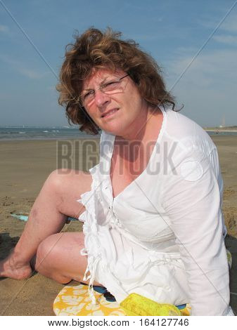 A Retired Senior Woman On The Beach On Vacation